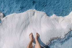 Men's feet on white calcite travertines with mineral water from thermal springs in Pamukkale, Turkey. The concept of Spa resorts and health of legs and feet