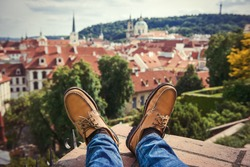 Men`s feet wearing brown leather shoes relaxing on the rooftop in old town of Prague