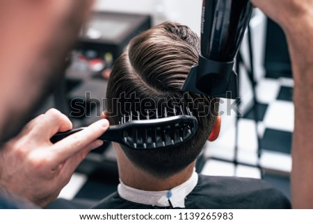 Men's haircut and styling in barbershop. Stylish Haircut Haircut.