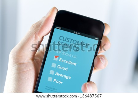 Men's hand holding modern mobile phone with customer service survey form on a screen. Red tick on excellent choice showing customer satisfaction.