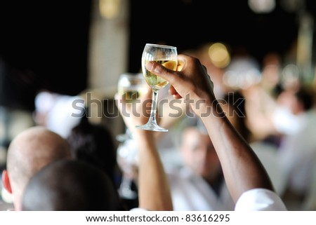 Men's hand holding wine glass at festive event