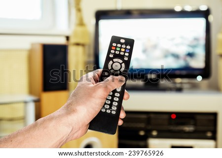Men\'s hand sends the remote control on the TV in the living room