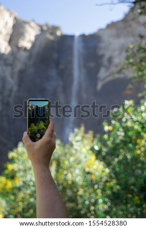 Men's hand takes phone and  photographs waterfall