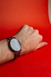 men's hand with a watch on a red background