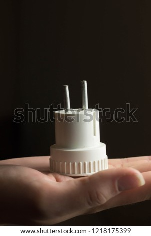 Men's hands are Plug in power outlet adapter cord charger of appliances #1218175399