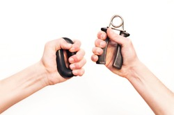 Men's hands compete with each other, measured by force. The hands hold the expander for training the force on white background. Hands grip strengthening tools