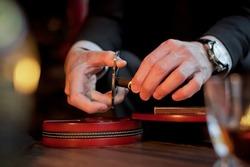 Men's hands cut a cigar with scissors. On the table lies a cigar, a lighter, a clock.