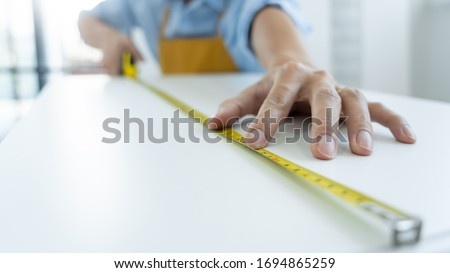 Men's hands hold a measuring tape measuring with flexible ruler for home renovation. repair, architecture and home renovation building and home concept ストックフォト ©