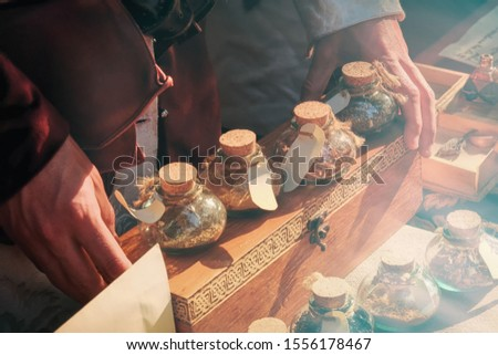 Men's hands holding a magic bottle of potion. Dry herbs and ingredients for mystical spells are sold in vintage shop