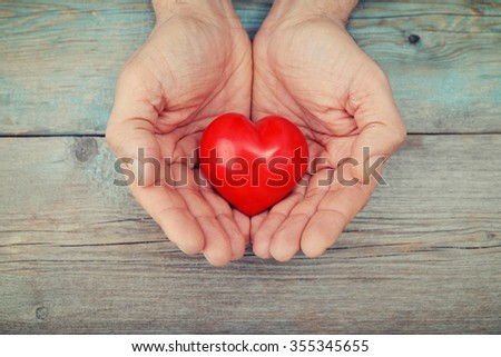 Men's hands holding decorative stone heart over wooden background #355345655