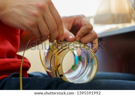 men's hands make a stained-glass window on glass vase or lamp, creating a handmade interior decoration, stained glass technique, side view, backlight