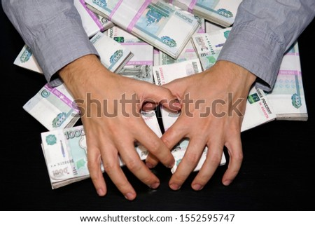 men's hands reach for a wad of money. A million rubles on the black table. The concept of wealth, success, greed and corruption, lust for money Foto stock ©