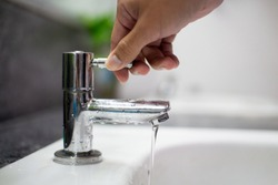 Men's hands turn off the tap to reduce global warming from turning on the waste water.