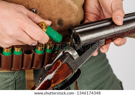 Men's hands with a hunting gun reload the cartridge #1346174348