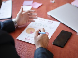 Men's hands work with documents on the wooden table. Business concept.
