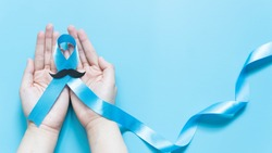 Men's health and Prostate cancer awareness campaign in November. Man hands holding light blue ribbon awareness w/ mustache on blue background. Symbol for support men who living w/ cancer. Copy space.
