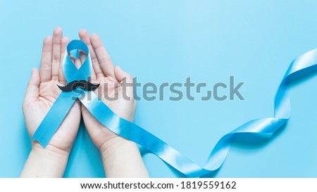 Men's health and Prostate cancer awareness campaign in November. Man hands holding light blue ribbon awareness w/ mustache on blue background. Symbol for support men who living w/ cancer. Copy space. Foto d'archivio ©