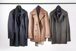 Men's jackets hanging on a rack. Men's jackets isolated on white background.