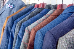 Men's jackets on hangers in the men's store. Row of men's suit jackets hanging in closet.