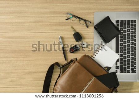 Men's leather bag with personal items and laptop on wood desk.