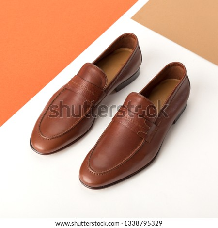 Men's leather loafers on a colored background. Geometric colored shapes background