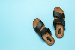 Men's leather sandals on a light blue background. Summer men's shoes. Flat lay.
