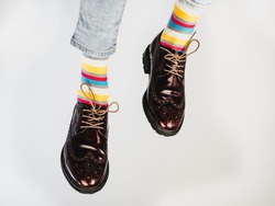 Men's legs in bright, striped, multi-colored socks and stylish, vintage shoes on a white, isolated background. Close-up. Concept of style, fashion and beauty