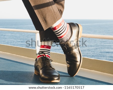Men's legs in stylish, black shoes, dark pants and funny, bright, striped socks with a pattern on the deck of a cruise ship. Concept of lifestyle, fashion and fun