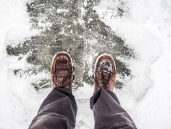 Men's legs in vintage leather boots on the frozen lake