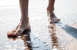 Men's legs on the beach. Holiday concept