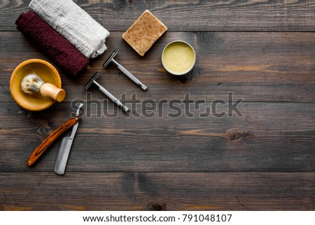 Men's shaving. Razor and brush on dark wooden background top view copy space