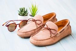 Men's summer shoes on blue wooden board