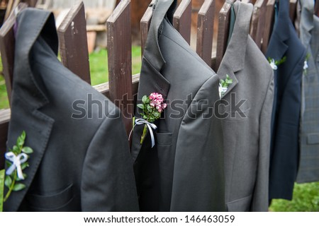Men's wedding jackets hanging in a row on a wooden fence. Shallow DOF