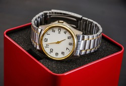 men's wristwatch in a red box on a black background. Close-up.