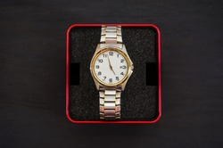 men's wristwatch in a red box on a black background. View from above.