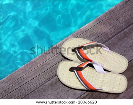 men sandals on a wooden floor with flowers near the water