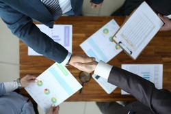 Men shake hands over the table with reports. Marketing and branding add value and attract new customers. Launching and calculating project profitability. Financial officials discuss report
