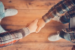 Men shaking hands. Top view of two men shaking hands while standing on the wooden floor