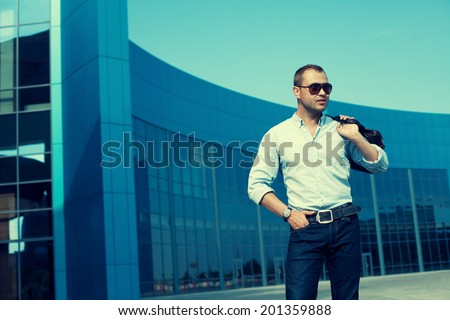 Men Shopping concept. Profile portrait of attractive smiling man in trendy casual clothing with sunglasses and leather bag posing over shopping mall. Sunny spring weather with blue sky. Outdoor shot