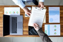 Men sign contract on background documents devices. Source information for persons directly implementing project. Marketing optimization with graph and chart reports. Market demand and contract