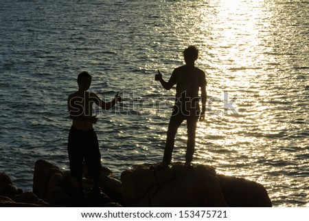 Men silhouette in victory action over sea sunset