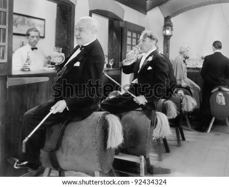 Men sitting at a bar on horse back