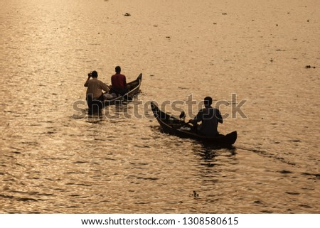 men sitting in dugout canoes in sunrise lit water paddle down the river