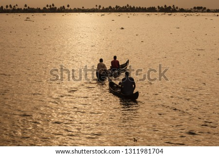 men sitting in dugout canoes in sunrise lit water travel down the river