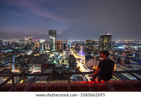 Men sitting on the rooftop Mexico city with night downtown view. Mexico City skyline at night from top #1060662695