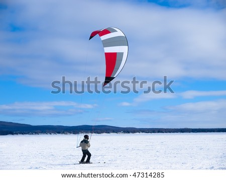Men ski kiting on a frozen lake