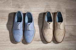 Men suede shoes on the wooden floor. blue and beige shoes isolated.