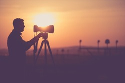 Men Taking Outdoor Pictures During Scenic Sunset. Photographer Silhouette. Telephoto Lens and the Modern Camera on a Tripod.