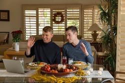 Men Talk on Video Call Through a Laptop at Dinner