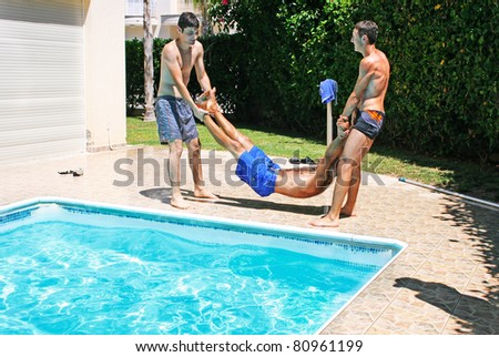 Men  throwing  their friend to swimming pool.